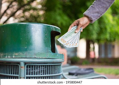 Closeup cropped portrait of someone hand tossing cash dollar bills money, hundred dollar bills in trash can, isolated outdoors green trees background. Bad financial investment decisions concept