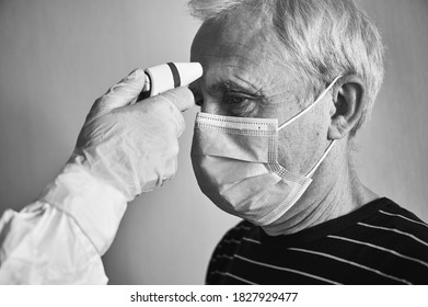 Close-up cropped snapshot of doctor's hand in glove and PPE suit measuring old man's fever with infrared contactless thermometer, patient's head in mask, black and white. COVID-19 concept