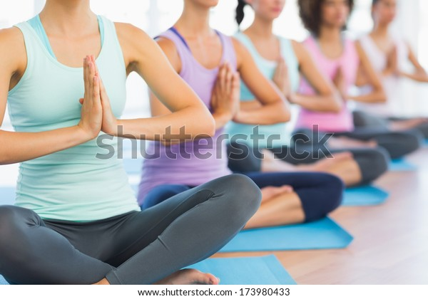 Closeup of cropped sporty women with joined hands at a bright fitness studio