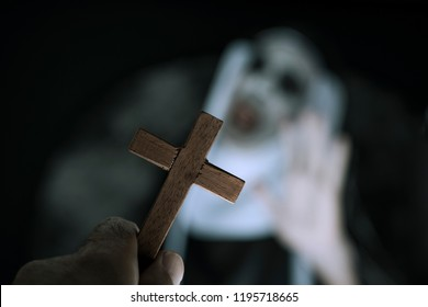 closeup a cross in the hand of a man and a frightening evil nun, wearing a typical black and white habit, screaming
