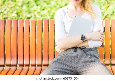 Closeup of crossed arms female wearing a wristwatch and holding a tablet while siting on a park bench.