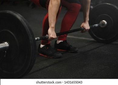Closeup of crossfit female athlete preparing for lifting weights at the gym. Woman hands holding barbell.