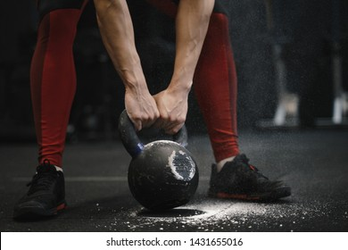 Closeup of crossfit woman lifting heavy kettlebell at gym. Copy space