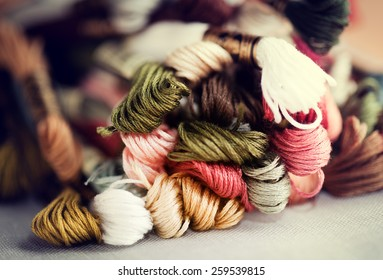 Closeup of cross-stitching skeins with selective focus and shallow depth of field