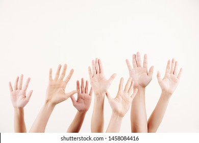 Close-up of crowd of people stretching their hands up they voting over white background