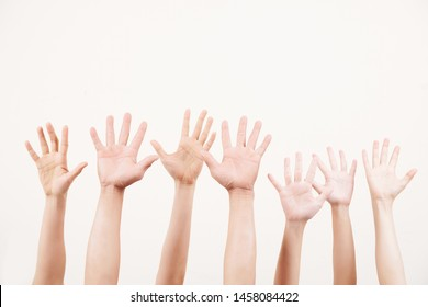 Close-up of crowd of young people stretching their arms up and voting together over white background