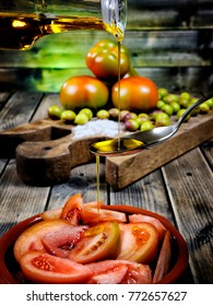 Close-up of an cruet pouring olive oil over tomato salad on an antique wooden table