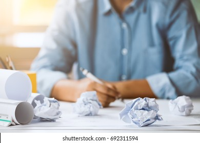 Close-up of crumpled paper on table with unhappy businesswoman was frustrated. Concept of no idea to thinking