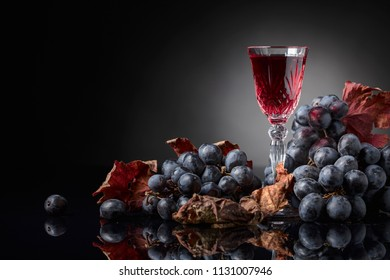 Close-up of crystal glass with red wine on dark background. Dark grapes with dried vine leaves. Selective focus, free space for your text.