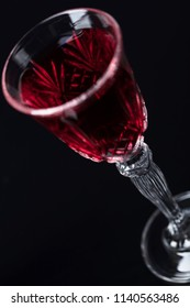 Close-up of crystal glass with red wine on dark background. Free space for your text. Selective focus.