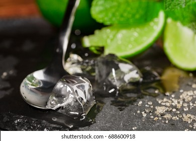 Close-up of crystal ice, brown sugar, silver spoon and bright juicy lime segments with mint segments. Ingredients for cocktails.