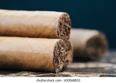 Close-up of Cuban cigars on brown marble.