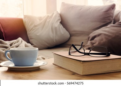 closeup of cup and book with eyeglasses on wooden table in front of couch in living room