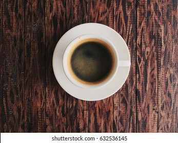 Closeup cup of coffee americano , black coffee on wood table brown color  , space for work