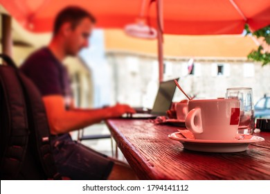 Closeup of a cup of coffee at a dalmatian coffee shop, blurred man sitting on a laptop working, concept of software developers working while travelling and being on standby