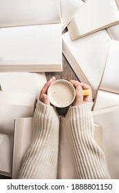 close-up of a cup of coffee in hands of woman on background of open books. top view
