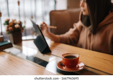 Close-up of a cup of dark coffee on a table in a cafe. In the background sits a young woman in casual clothes and works at a digital tablet.