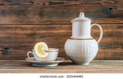 Closeup of a cup of green tea with a lemon slice and teapot on wooden background.