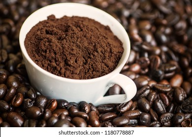 Closeup of a cup of ground coffee on the heap of roasted coffee beans, shot in the studio