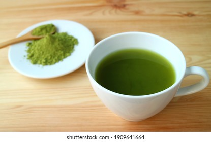 Closeup a Cup of Hot Matcha Green Tea on Wooden Table with Blurry Matcha Tea Powder in Background
