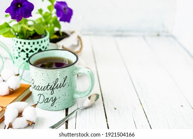 Close-up of a cup of tea on a wooden white table with blurred background, front blur. Still life with flower, book, teaspoon, cotton box.