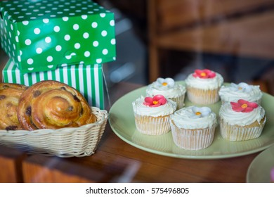 Close-up of cupcakes, desserts and boxes on display counter in supermarket