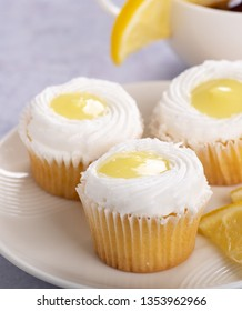 Closeup of cupcakes with lemon filling and white icing on a  plate