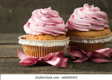 Closeup of cupcakes with vanilla, berries, pink and white cream, chocolate and sprinkles on wooden background. Selective focus. Sweet dessert tasty food concept muffin.