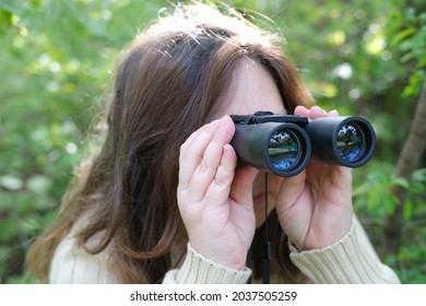 close-up curious European adult woman holding black field glasses with zoom, hiding in greenery, peeping from green bushes, spying on unfaithful husband, neighbors