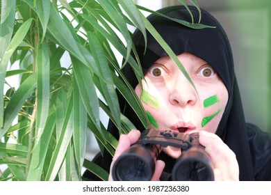 close-up curious islamic woman in war paint, holding field binoculars with zoom, peeping from the bushes, spying on unfaithful husband, neighbors