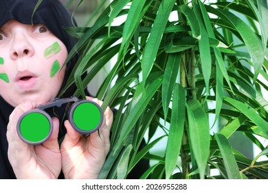 close-up curious islamic woman in war paint, holding field binoculars with zoom, chromakey lenses, peeping from the bushes, spying on unfaithful husband, neighbors