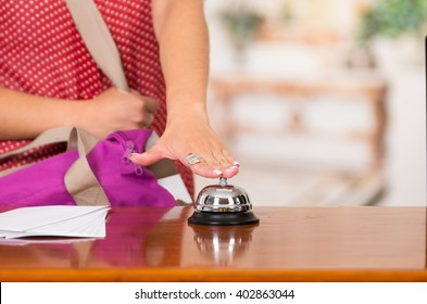 Closeup customer guest and hotel receptionist interacting at front desk, bell sitting on table, exchanging room key