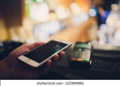 Closeup of a customer using her bank card and nfs technology to pay a barista for her purchase at a cafe.