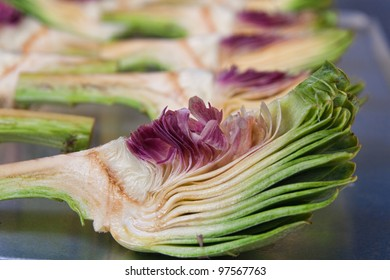 closeup of cut artichoke with more in the background out of focus