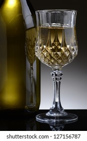 Closeup of a cut crystal glass of white wine and bottle against a light to dark gray background.