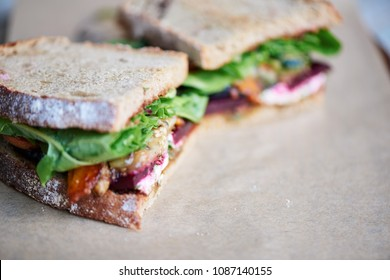 Closeup of a cut in half sandwich with assorted organic vegetables resting on a piece of paper and board on a wooden table