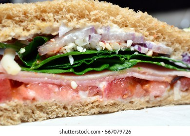 Closeup cut side view of fancy ham sandwich on napkin