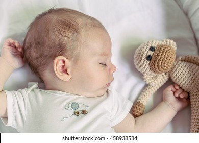 Close-Up Of Cute 4-Month Newborn Baby Boy Sleeping With His Monkey Toy