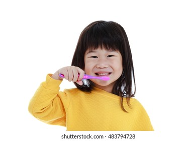 Closeup cute asian girl in pajamas with a toothbrush in hand smiling and go to brush teeth, oral health concept. Isolated on white background. Sleepy chinese child waking up early in the morning.