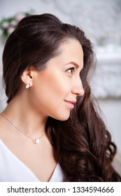 Closeup cute beautiful brunette girl with long hair in silver jewelry earrings and a necklace. Сoncept of gentle, elegant, delicate, romantic jewelry, bijouterie on the model