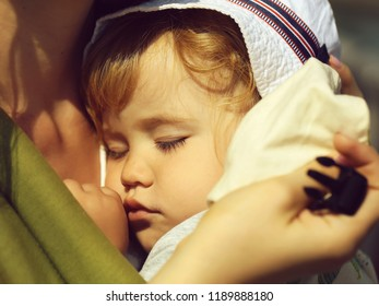Closeup of cute beautiful carefree innocent baby boy deep sleeping on hands of mother sunny day outdoor, horizontal picture