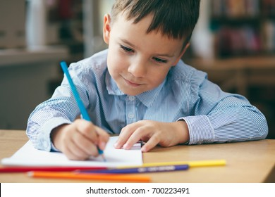 Close-up, cute  boy doing homework,  coloring pages, writing and painting. Children paint. Kids draw. Preschooler with books at home. Preschoolers learn to write and read. Creative boy.