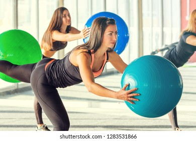 Close-up cute brunette girl in black tight leggings do exercise with fitball in her hands bending forward on background other fitness women