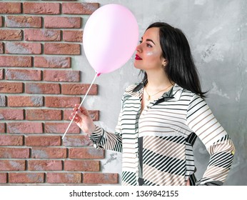Close-up of cute brunette girl standing in a studio, smiling widely and playing with pink baloon. Girl in shirt. Concept for bithday, womans day. Selective focus. Mockup for balloon