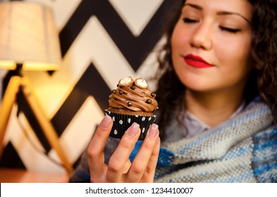 Closeup of cute curly hair girl holding and smelling chocolate cupcake, hedonism
