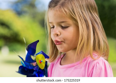 Close-up of cute girl blowing pinwheel at the park
