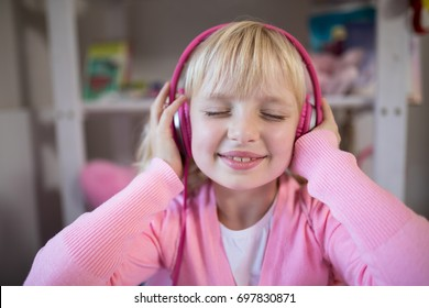 Close-up of cute girl listening to pink headphones