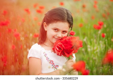 Closeup of cute girl in poppy field holding flowers bouquet outdoors. Girl in poppies. Happy kid with poppies.