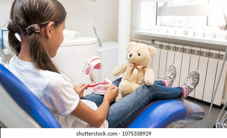 Closeup of cute girl sitting in dentist chair and playing with her teddy bear in doctor and patient