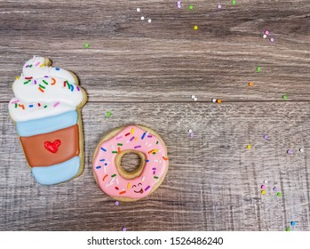 Closeup of cute happy latte and donut sugar cookies on a wooden background with sprinkles celebrating the day
